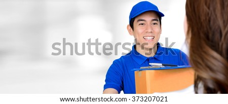 Smiling delivery man delivering a package on blur white panoramic background with copy space - stock photo