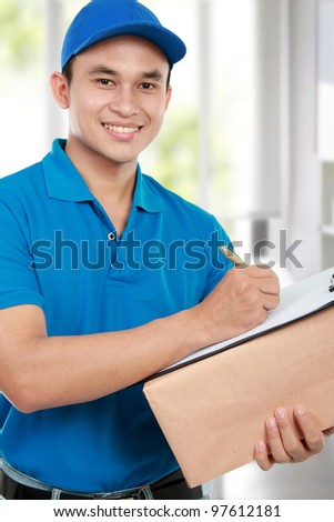 smiling delivery man in blue uniform with packages and clipboard