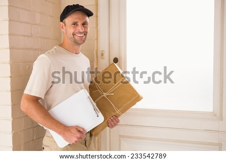 Smiling delivery man with box and clipboard outside the warehouse - stock photo