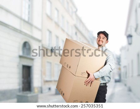smiling delivery man with boxes - stock photo