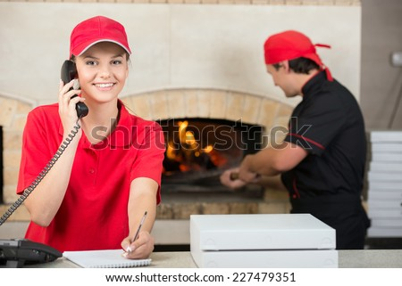 Smiling delivery woman of pizza on the phone and chef baker with long handled bread pan baking pizza into wood fire oven done. - stock photo