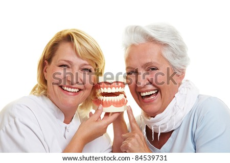 Smiling dentist and senior woman with a teeth model