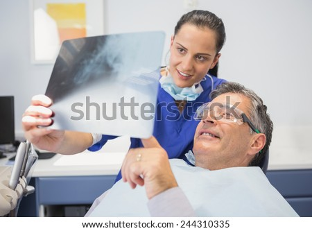 Smiling dentist showing x-ray to her patient in dental clinic