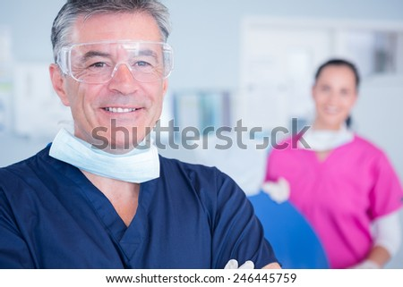 Smiling dentist with protective glasses at the dental clinic - stock photo