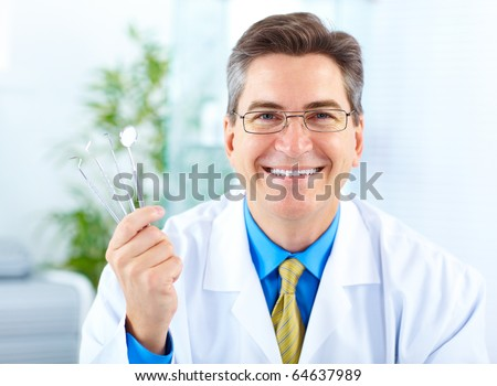 Smiling dentist with tools in the office - stock photo