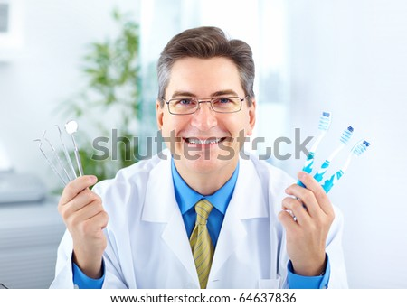 Smiling dentist with toothbrushes in the office - stock photo