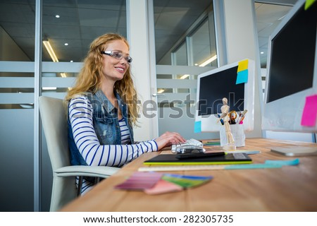 Smiling designer sitting at her desk and typing on keyboard in the office - stock photo
