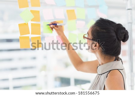 Smiling designer writing on sticky notes on window in creative office - stock photo