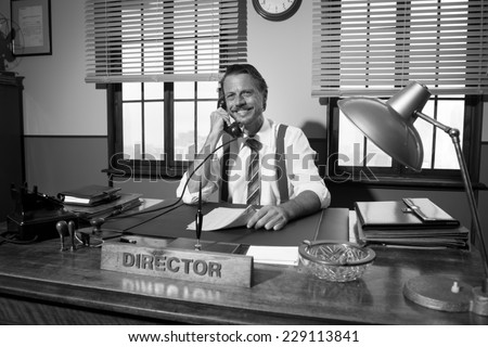 Smiling director working at desk having a phone call, 1950s style office. - stock photo