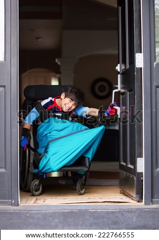 Smiling disabled boy in wheelchair opening front door - stock photo