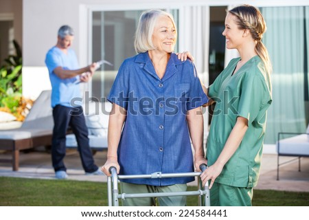 Smiling disabled senior woman and nurse looking at each other in lawn at nursing home - stock photo