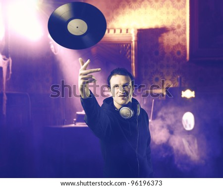 Smiling disc-jockey throwing a long play record in a discotheque - stock photo