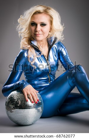 smiling disco girl is posing with the mirror ball - stock photo