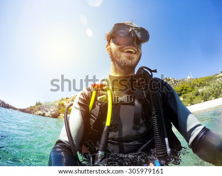 Smiling diver portrait at the sea shore. Diving goggles on. - stock photo