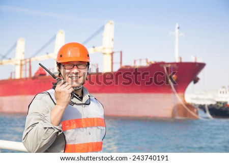 smiling dock worker holding  radio and  ship background - stock photo