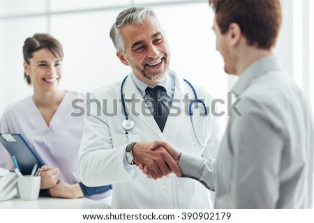 Smiling doctor at the clinic giving an handshake to his patient, healthcare and professionalism concept - stock photo