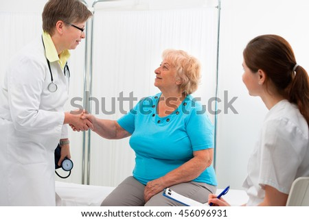 Smiling doctor at the office giving a handshake to her patient - stock photo