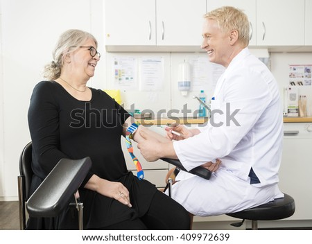 Smiling Doctor Collecting Senior Patient's Blood For Test In Clinic - stock photo