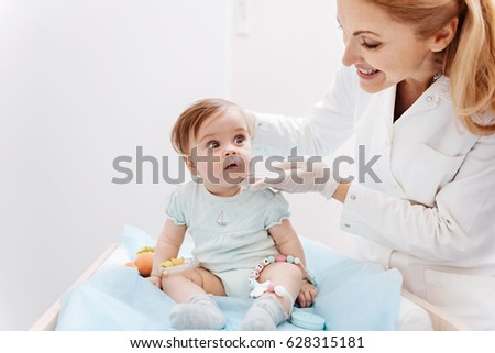 Smiling doctor doing child examination