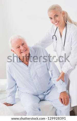 Smiling doctor helping elderly man to sit up - stock photo