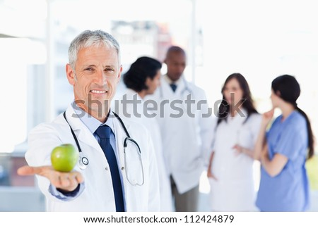 Smiling doctor holding a green apple in his right hand - stock photo