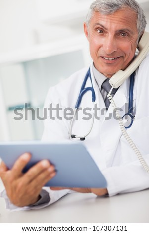 Smiling doctor holding a tablet computer and calling in medical office - stock photo