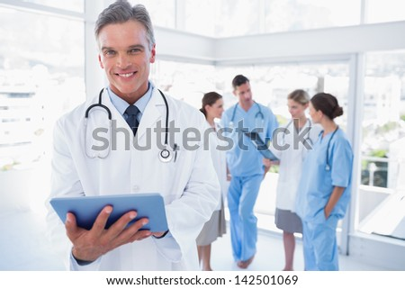 Smiling doctor holding digital tablet in front of his medical team - stock photo