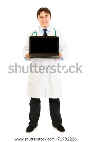 Smiling  doctor holding laptop with blank screen in hands  isolated on white - stock photo