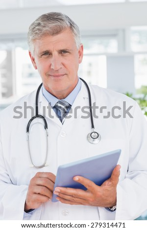 Smiling doctor holding tablet in medical office - stock photo