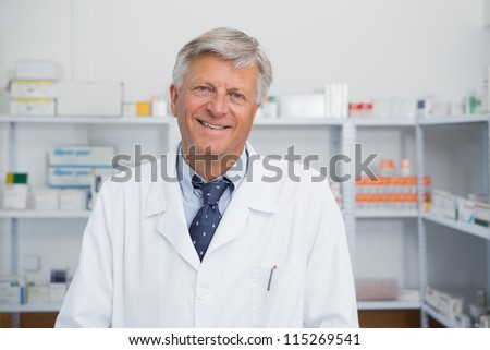 Smiling doctor in a hospital pharmacy - stock photo