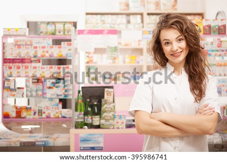 Smiling doctor in front of pharmacy desk. Healthcare business - stock photo