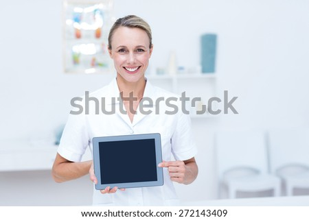 Smiling doctor looking at camera and showing tablet in medical office - stock photo