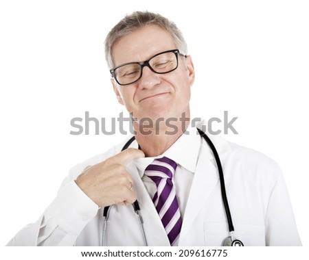 Smiling doctor loosening his tie by inserting his finger in the neck of his shirt as he reacts to the pressure and stress or to try to cool down on a hot day, isolated on white