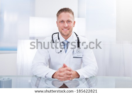 Smiling doctor or consultant sitting at a desk with his stethoscope around his neck looking at the camera - stock photo