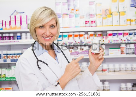 Smiling doctor pointing a drug bottle in the pharmacy - stock photo