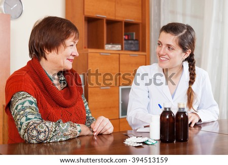 Smiling doctor prescribing medication to senior woman at table - stock photo