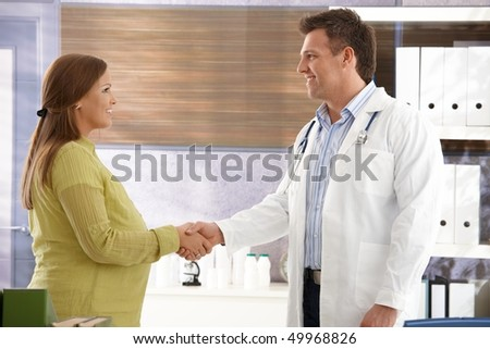 Smiling doctor shaking hands with pregnant woman in consulting room. - stock photo