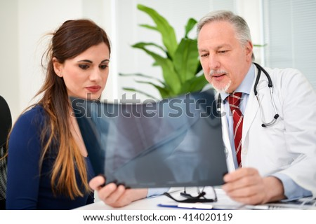 Smiling doctor showing a radiography to his patient - stock photo