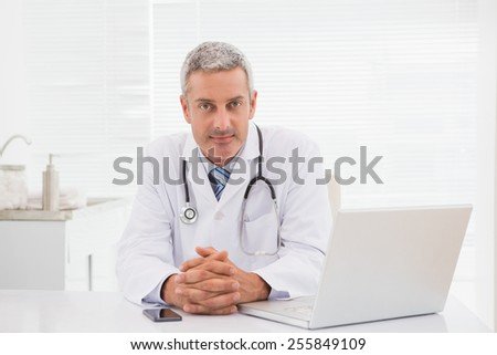 Smiling doctor sitting at his desk in medical office - stock photo