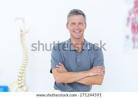 Smiling doctor standing arms crossed in medical office - stock photo
