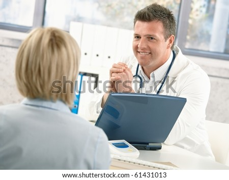 Smiling doctor talking to patient at office desk. - stock photo