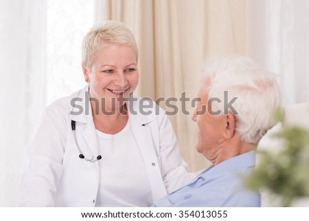 Smiling doctor visiting her elderly patient at home