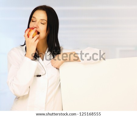 Smiling doctor with apple and blank banner isolated