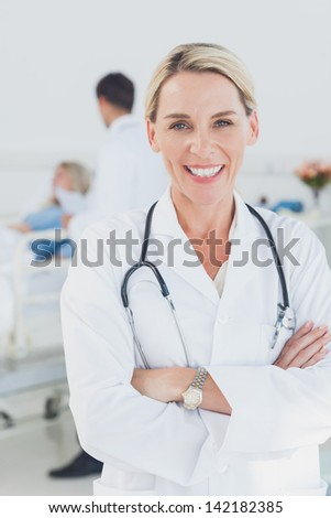 Smiling doctor with arms crossed in front of a patient and a doctor - stock photo