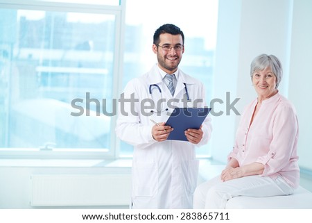 Smiling doctor with clipboard and his patient looking at camera - stock photo