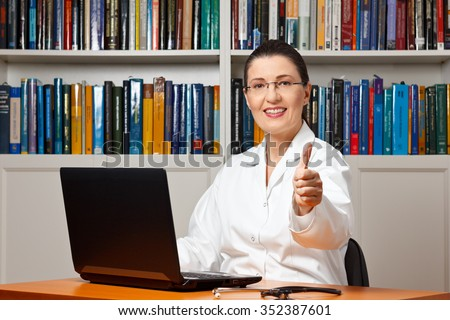 Smiling doctor with computer and a lot of books showing thumbs up, best, top online medical advice, remote health care consultation, telemedicine - stock photo