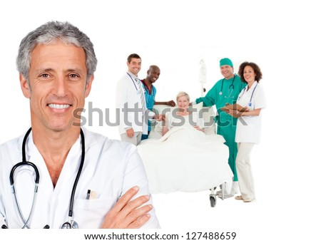 Smiling doctor with patient in bed and medical staff behind him on white background