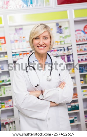 Smiling doctor with stethoscope and arms crossed in the pharmacy - stock photo