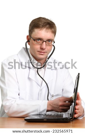 Smiling doctor with stethoscope working on a laptop against white background