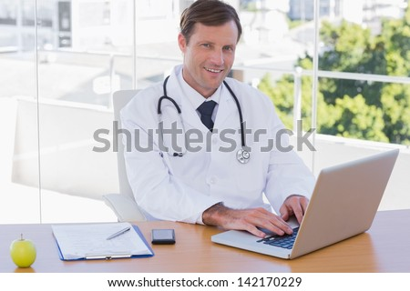 Smiling doctor working on a laptop on his desk - stock photo